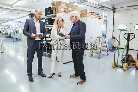 senior businessman discussing over machine part