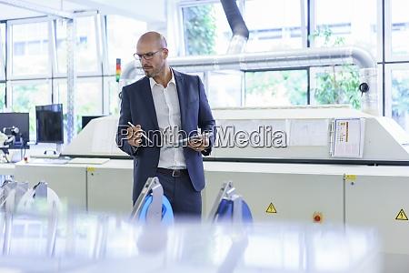 mature male professional holding digital tablet