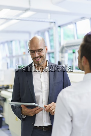 smiling businessman looking at digital tablet