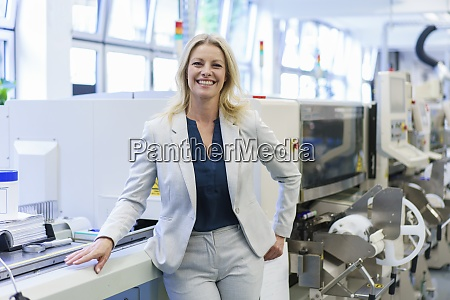 smiling mature blond businesswoman standing by