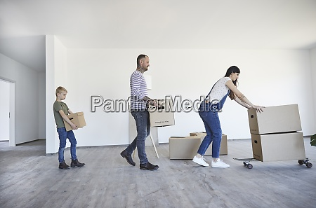 family keeping cardboard boxes on skateboard