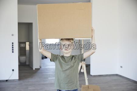 little boy carrying cardboard box on