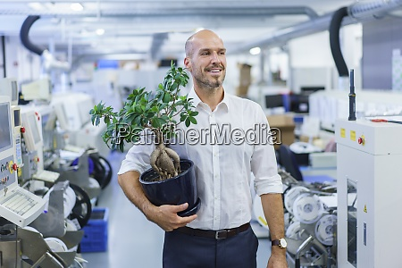 smiling businessman holding potted plant while
