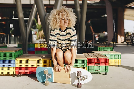 afro blond woman holding skateboard and