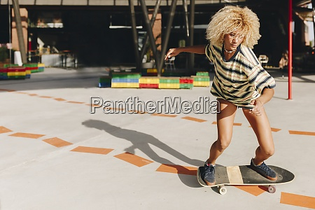 confident blond woman skateboarding on footpath