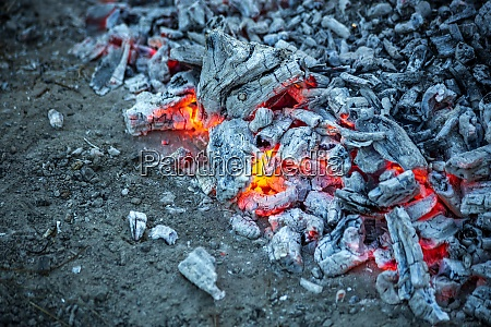 embers burning in campfire ash