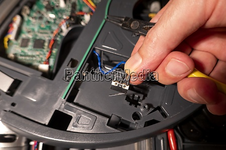 hand of mature man repairing robotic