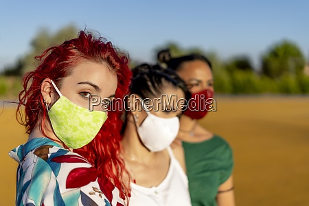 friends wearing protective face mask while