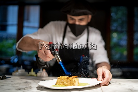 chef preparing pudding while giving flame