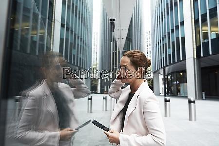 mature female entrepreneur holding smart phone