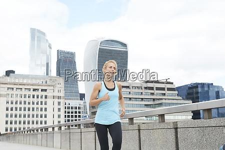 mature blond woman running on footbridge