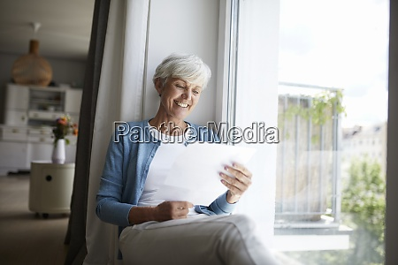 senior woman reading letter happily while