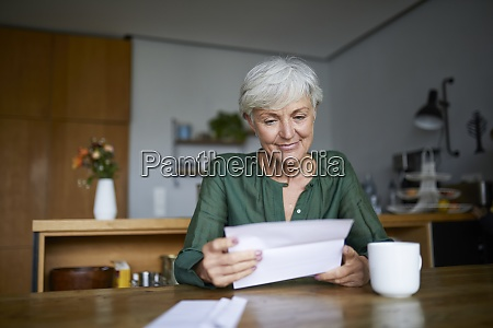senior woman reading letter while sitting