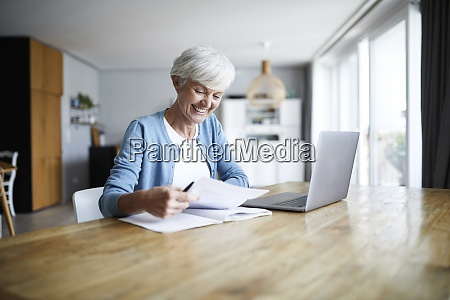 smiling active senior woman doing paper
