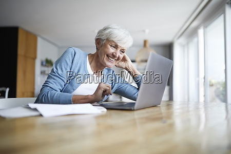 smiling senior woman with hands behind