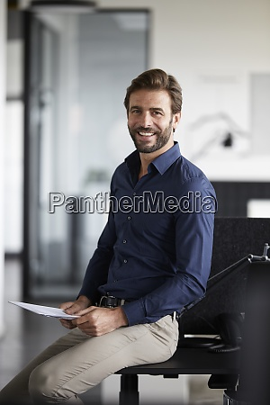 smiling businessman holding paper while sitting