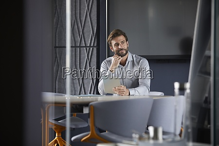 thoughtful businessman holding digital table while