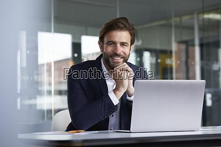 smiling businessman using laptop while sitting