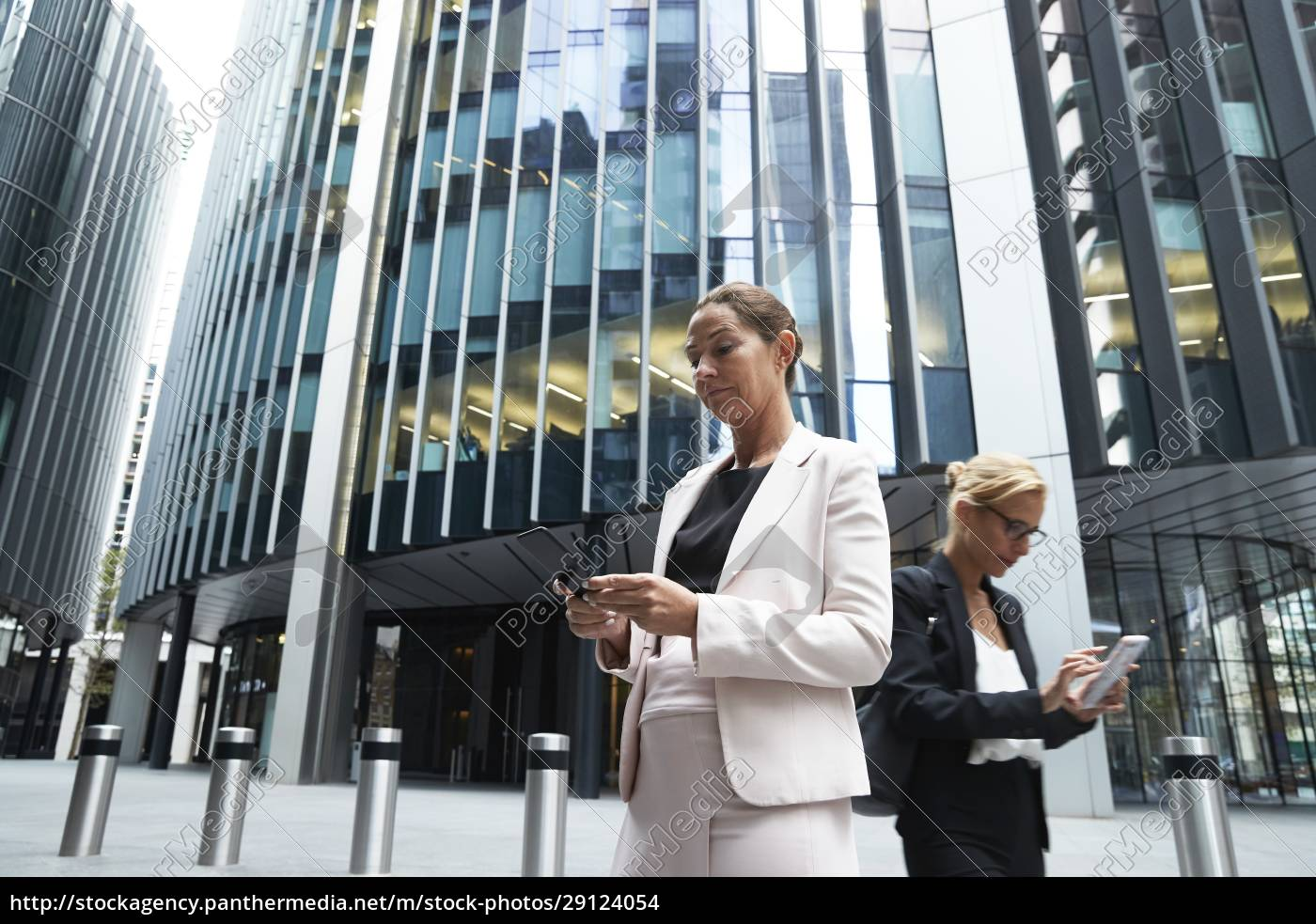 mature, businesswomen, using, smart, phones, against - 29124054