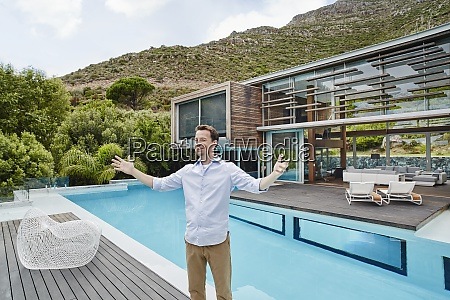 cheerful mature man standing against modern