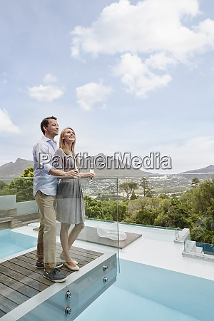 couple holding wine glass looking up