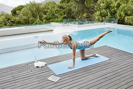 young woman practicing yoga near swimming