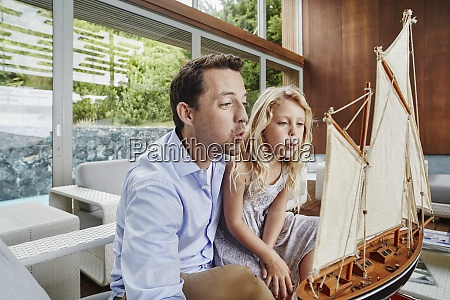father and daughter blowing toy boat