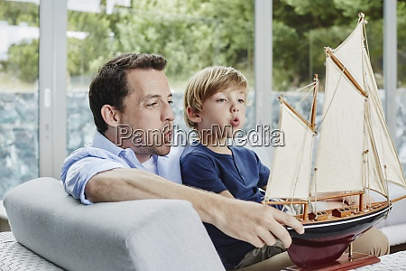 father and son blowing toy boat