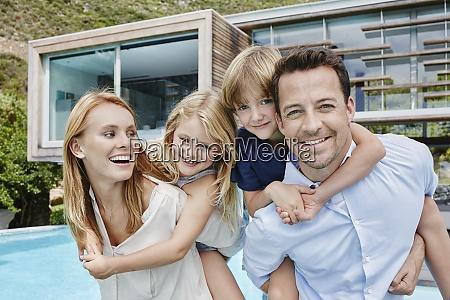 family standing against modern house