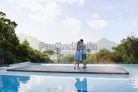 heterosexual couple kissing while standing on