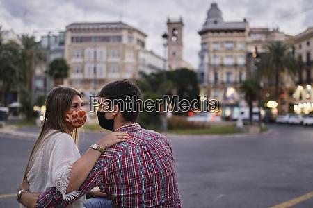 couple wearing protective mask sitting on