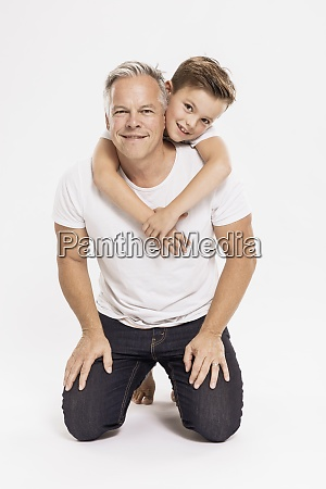 cute boy embracing father kneeling against