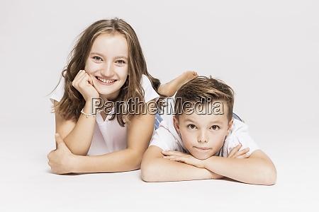 cute siblings lying on white background