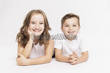cute smiling siblings lying on white