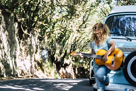 mature woman wearing sunglasses playing guitar