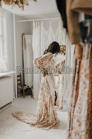 young bride trying on wedding dress