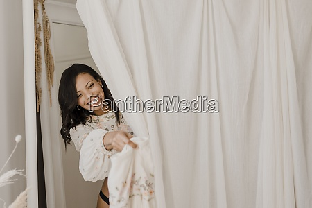 smiling bride changing dress behind curtain
