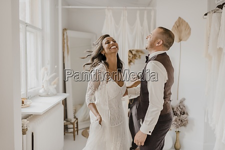 heterosexual couple laughing while dancing at