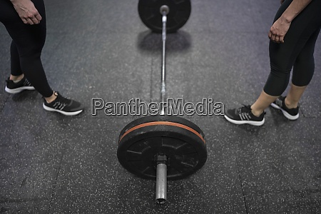 female athlete standing by barbell at