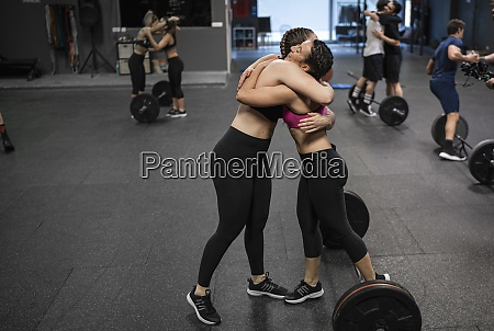 athletes hugging each other while standing