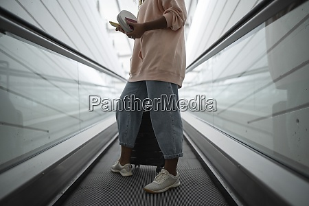 legs of woman standing on escalator