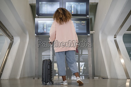 young woman checking for flight schedule