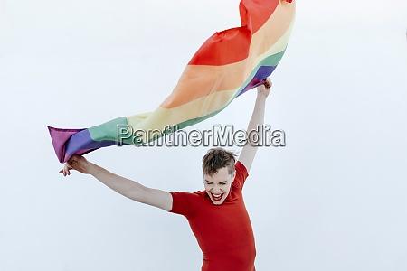 non binary person waving multi colored