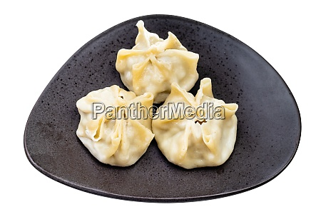 three steamed buuz on black plate