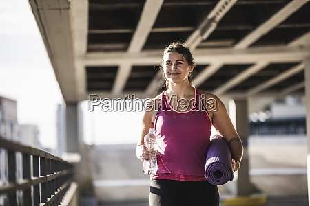 confident young woman holding mat and