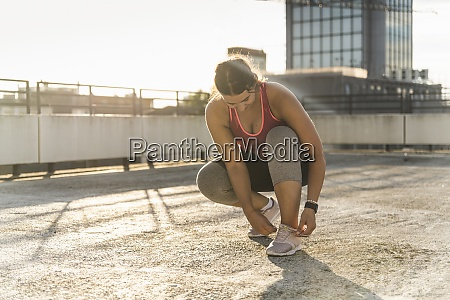 young woman tying shoelace while crouching