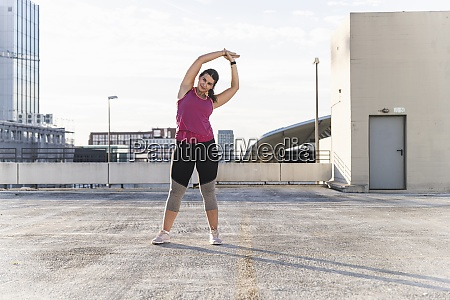 young woman with arms raised exercising