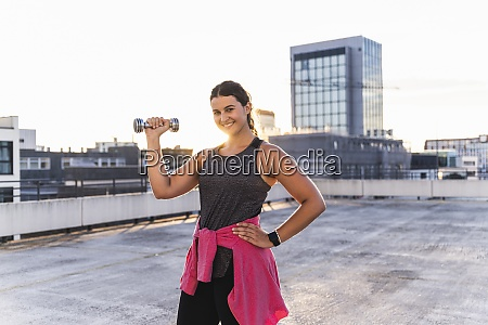 smiling young woman lifting dumbbell while