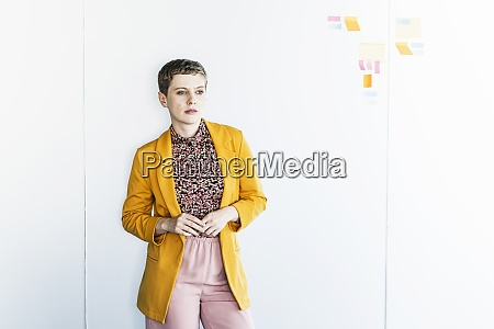 thoughtful businesswoman wearing blazer standing against