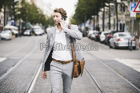 man with bag talking on mobile